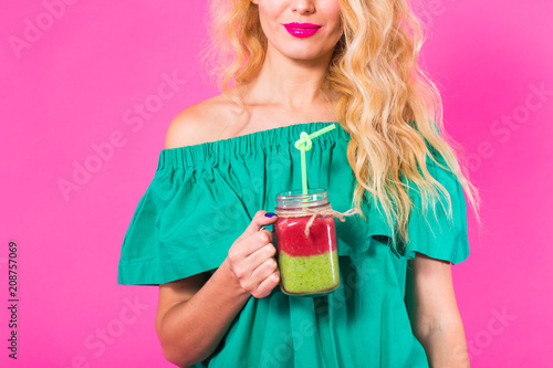 Leinwanddruck Bild Close up of woman with green smoothie on pink background