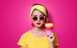 Girl in sunglasses and yellow t-shirt holding a red cup of coffee on pink background - 208757877