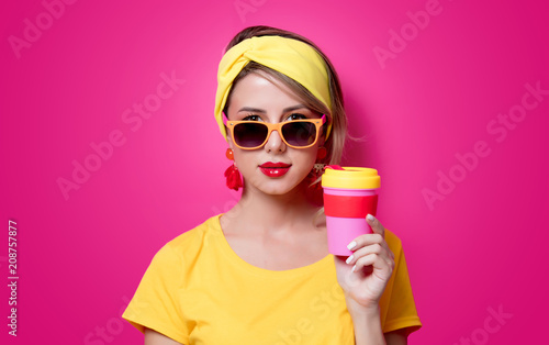 Wall mural Girl in sunglasses and yellow t-shirt holding a red cup of coffee on pink background