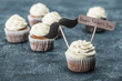 creamy cupcakes with mustache sign and Happy fathers day inscription on concrete surface