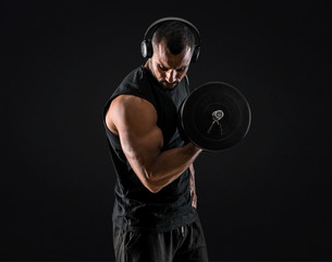 Strong handsome sport man making weightlifting, listening music and exercising the biceps on isolated black background