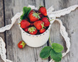 Fresh juicy strawberries with leaves. Rustic enameled mug and handmade lace. Retro magazine picture. - 208765212