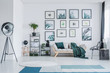Big studio lamp standing in white living room interior with wooden sofa with green pillow and blanket, gallery with simple posters, black racks with plants and decor and two carpets on the floor