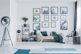 Big studio lamp standing in white living room interior with wooden sofa with green pillow and blanket, gallery with simple posters, black racks with plants and decor and two carpets on the floor - 208767093