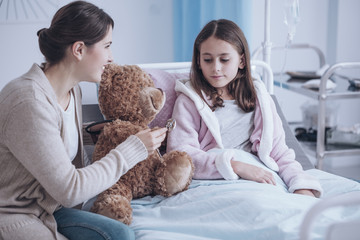 Smiling mother and weak daughter taking care of teddy bear in the hospital © Photographee.eu