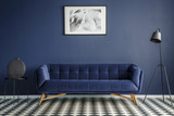 Navy blue room interior with comfortable plush couch in the middle, black lamp and side table with decoration standing on chessboard floor. Framed image on the wall. Real photo