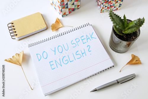 Do you speak english written in a notebook on white table