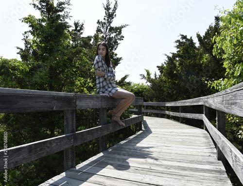 Young woman walking on boardwalk - 208768810