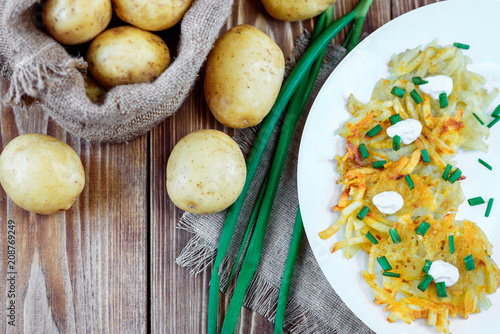 Fried potato pancakes or draniki with sour cream and green onion. The national dish of Belarus, Ukraine and Russia. - 208769249