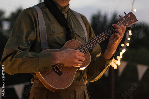 Man playing a ukulele outside on a summers evening - 208773475