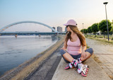 Roller girl resting after drive, sitting on concrete wall - 208783089