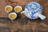 Hot tea pot with three ceramic cups on wooden table, top view - 208784073