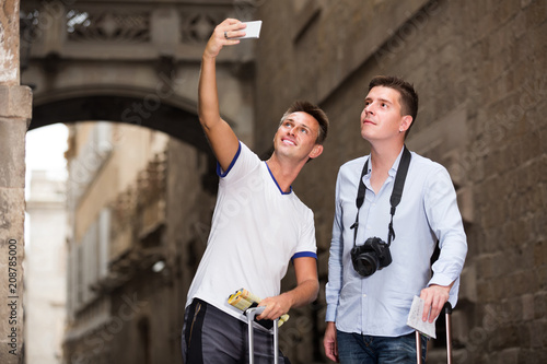 Sticker Two men with luggage doing selfie during city tour at vacation