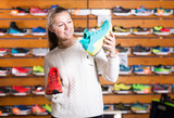 Portrait of young cute woman choosing sport shoes
