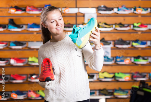 Leinwanddruck Bild Portrait of young cute woman choosing sport shoes