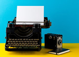 Vintage typewriter with empty, blank sheet of paper, camera and notebook on yellow and cyan - 208785831