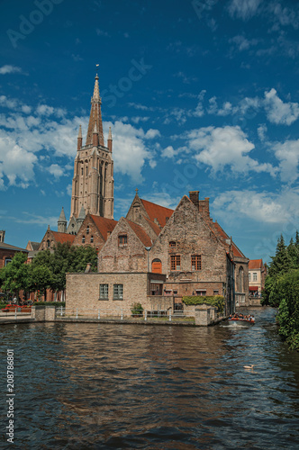 Fotobehang Brugge Steeple and old brick buildings on the canal's edge in a sunny day at Bruges. With many canals and old buildings, this graceful town is a World Heritage Site of Unesco. Northwestern Belgium.
