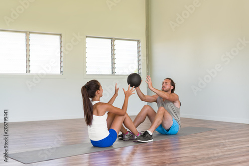 Poster Gym fitness couple training body core together throwing weight ball at each other during sit-ups on floor workout exercise mat. Fun friends activity.