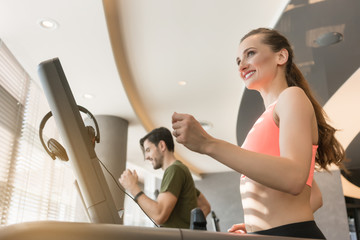 Happy young woman listening to music while running beside a handsome man on a modern treadmill with touch screen and headphones © Kzenon
