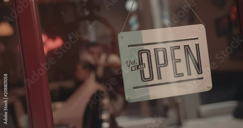 Open signboard on old-fashioned barber shop window with barber indoors