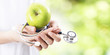 hands with Apple and stethoscope, healthy eating concept