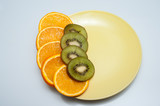 orange and kiwi slices spread on a plate - 208803645