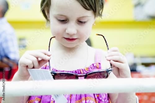 Little cute child girl trying sun eyeglasses