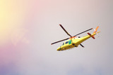 Yellow helicopter flying low above the ground against the sky