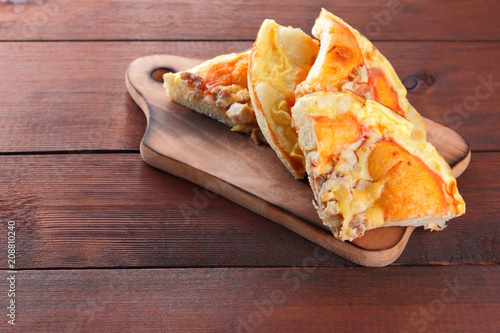 Homemade pizza on a wooden board, sliced pizza on a wooden background in rustic style, sandwiches with meat and cheese top view, delicious fast food at home kitchen, American cuisine, art - 208810240