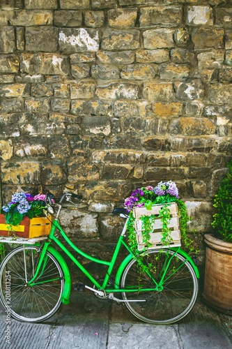Fotobehang Fiets Decorative bicycle with flowers against stone wall with copy space