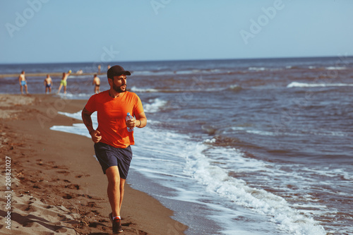 Fotobehang Hardlopen Young man jogging on the beach by the sea