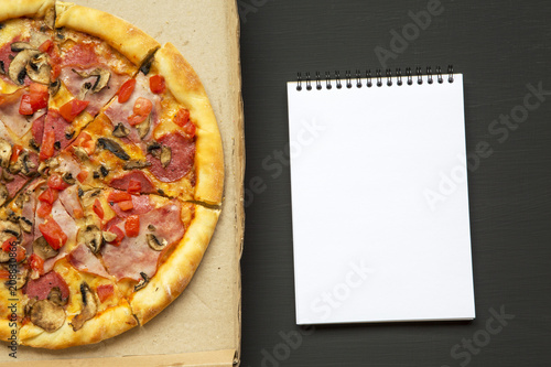 Aluminium Pizzeria Freshly baked pizza in a cardboard box with notebook over black background, top view. From above.