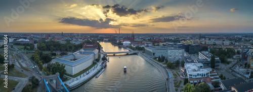 Widok z lotu ptaka na mosty, statek na rzece oraz zachodzące słońce - Wrocław, Polska - 208834064