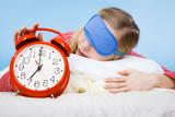 Sleeping woman wearing pajamas holding clock - 208835042