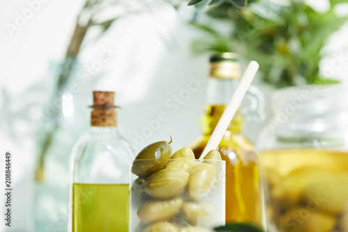 Leinwanddruck Bild closeup shot of glass with spoon and green olives, jar, various bottles of aromatic olive oil with and branches on wooden tray