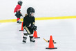 Little cute girl is playing hockey on ice wearing in full hockey equipment.  She does workouts with a stick and puck.