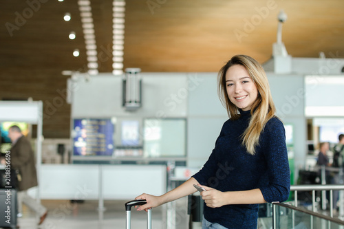 Pretty caucaisian woman typing message by smarphone at airport hall with valise. Concept of modern technology and flying abroad.