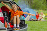Happy young girl in car near his camp tent at green field - 208866454