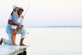 Father with his daughter fishing in a sea on a wood pier at sunset. - 208866874