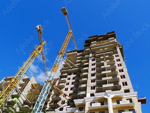 Dwa budowa żurawia i betonowy budynek w budowie przeciw niebieskiemu niebu. Budowa.