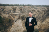 A stylish bridegroom in a black suit smiles against the background of gray rocks and hills. Autumn wedding portrait of a beautiful and young young groom. Film effect. - 208872682