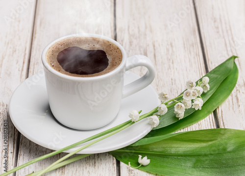 Foto Spatwand Lelietjes van dalen Cup of hot coffee and white lilies of the valley.