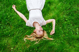 Beautiful young woman lying on the bright green grass. - 208873653