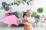 Little blonde girl in big hat standing in her room. Small girl and pink flamingo indoors - 208873669