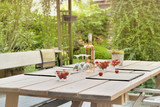 glasses, wine bottle and tomatoes on a table to a drink on a terrace in a garden  - 208879011