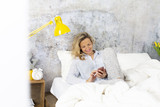 beautiful woman in the morning in bed with smartphone - 208879083