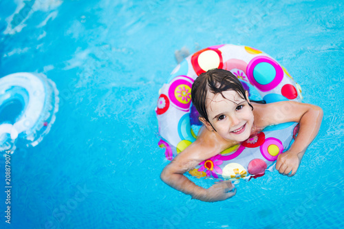 Foto Murales Little girl in swimming pool with float ring