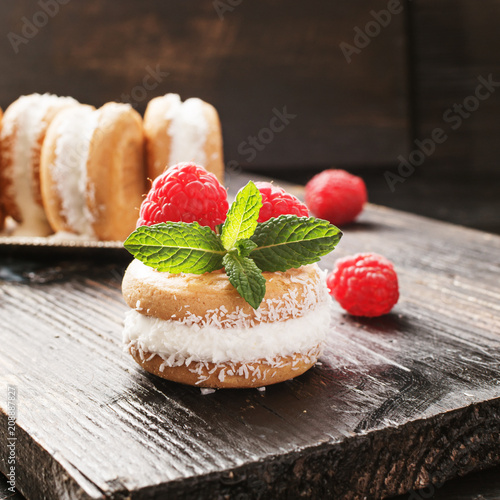 Ice cream cookie sandwiches with cocco and raspberries on wooden background.