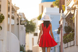 Santorini travel tourist brunette woman in red dress visiting famous white Oia village. - 208890667