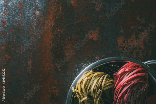 Foto Murales top view of green and red tagliatelle pasta in colander on rustic metal table